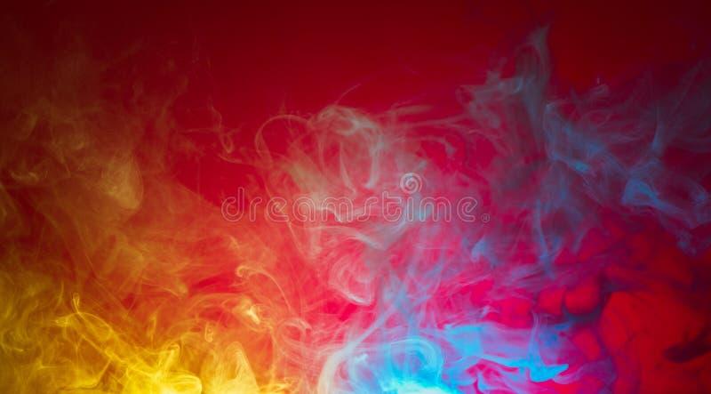 Humo amarillo y azul en fondo rojo foto de archivo libre de regalías