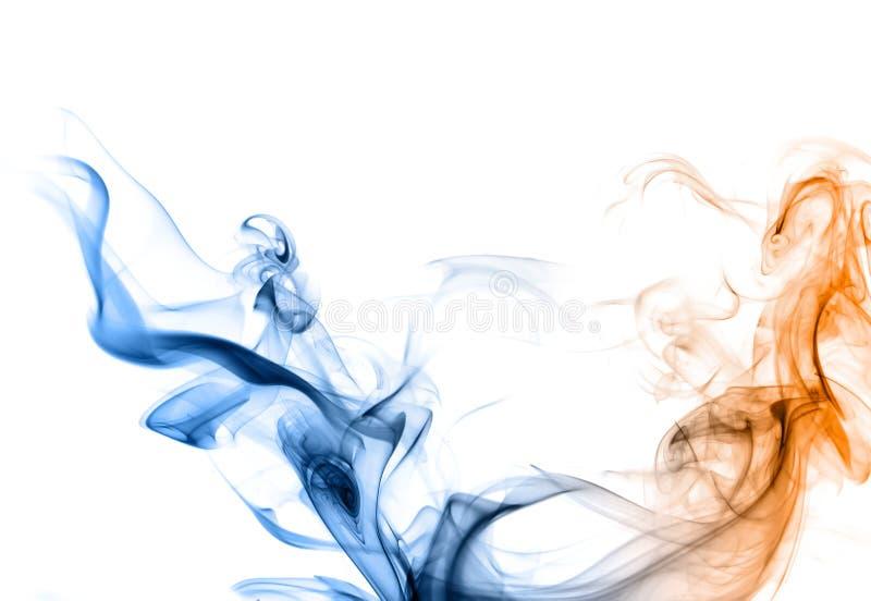 Humo azul y anaranjado en un fondo blanco. imagen de archivo libre de regalías