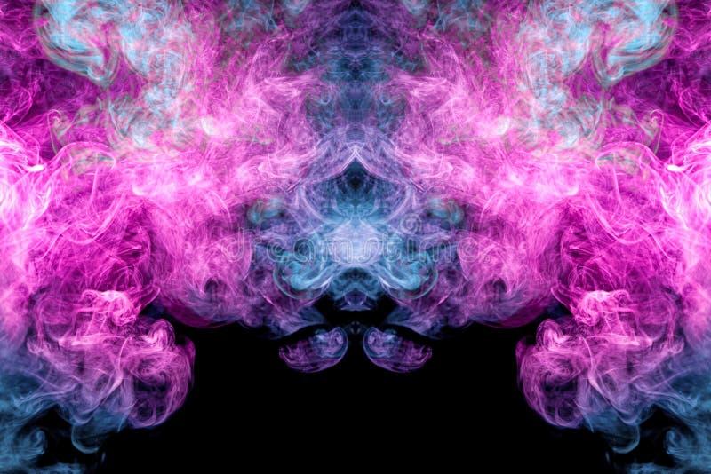 Humo azul y rosado del arte abstracto coloreado en fondo aislado negro imagen de archivo libre de regalías