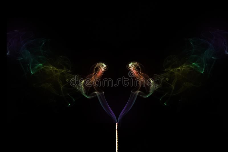 Humo coloreado que sale de los palillos del incienso Abstraiga el arte del humo foto de archivo