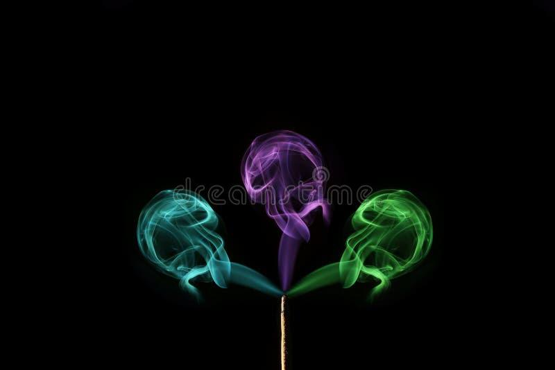 Humo coloreado que sale de los palillos del incienso Abstraiga el arte del humo imagenes de archivo