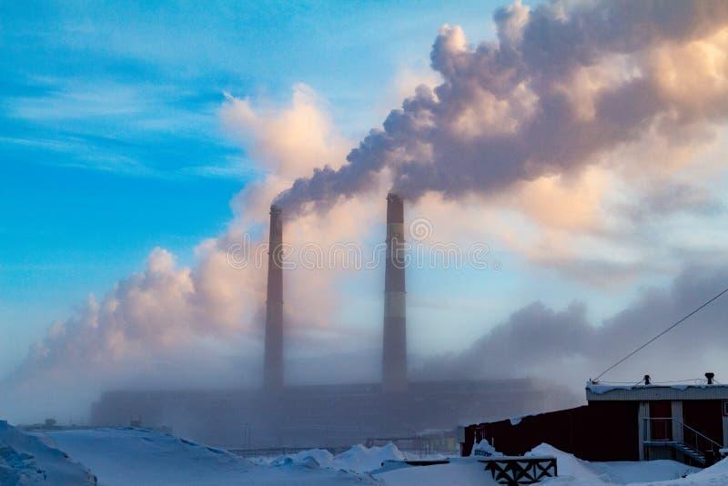 Humo del paisaje del invierno de las chimeneas contra el día brumoso escarchado del cielo azul Norilsk foto de archivo libre de regalías