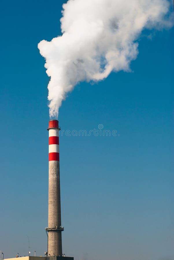 Humo industrial de la chimenea en el cielo azul imagenes de archivo