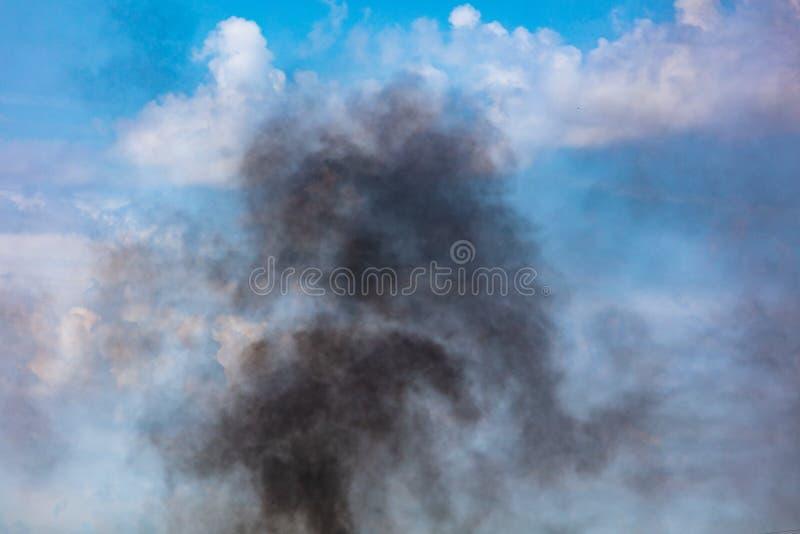 Humo negro contra un cielo azul con las nubes imagen de archivo libre de regalías