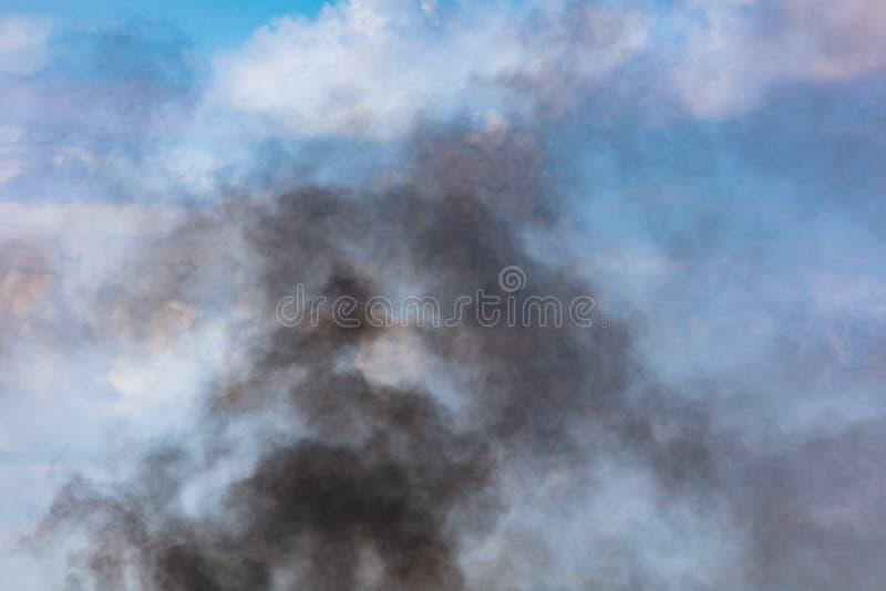 Humo negro contra un cielo azul con las nubes imagen de archivo
