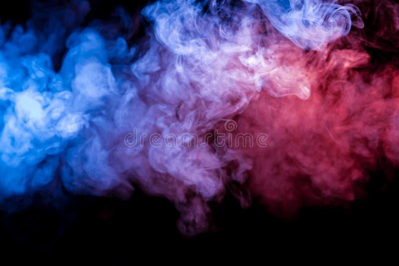Humo pesado multicolor de un vape del color azul y púrpura del exhalado por dispersado por los clubs en un fondo aislado negro foto de archivo