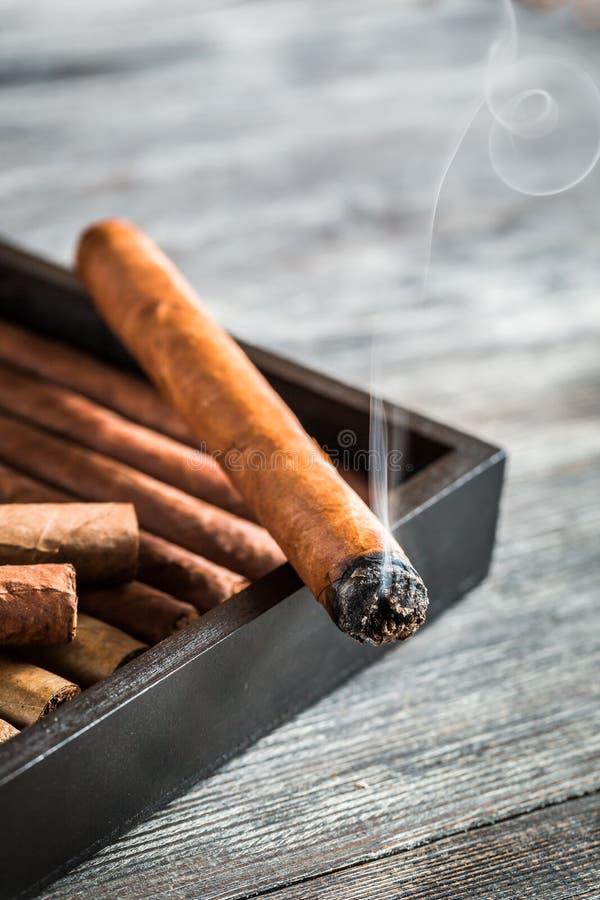 Humo que sube de un cigarro ardiente imagen de archivo