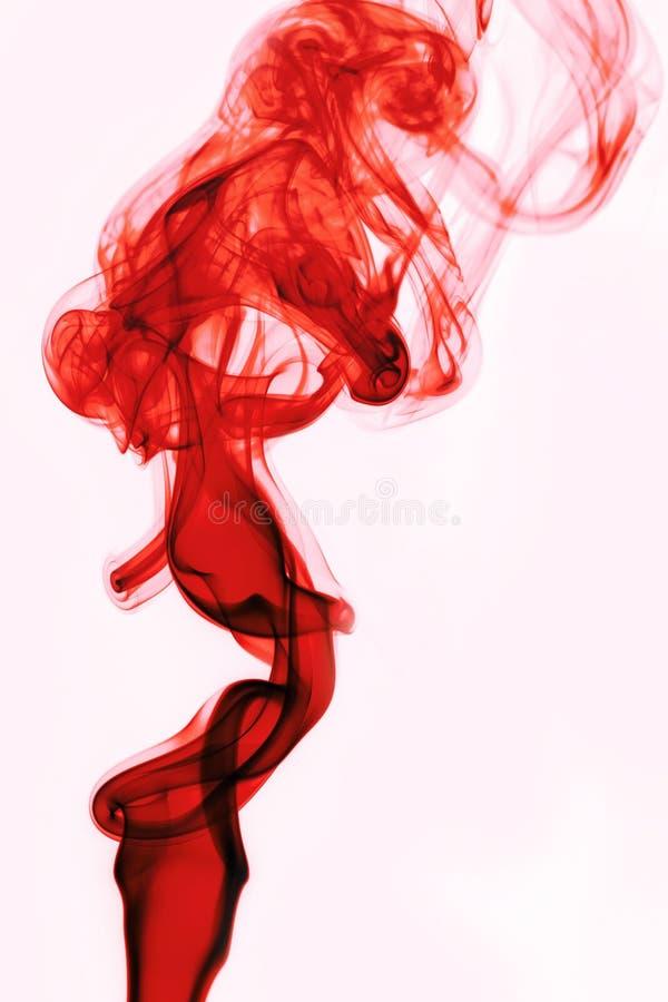 Humo rojo en el fondo blanco foto de archivo