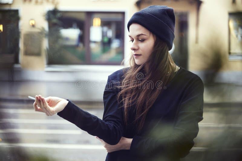 Humo solo hermoso de la mujer afuera en la calle, tiempo frío en una ciudad fotografía de archivo libre de regalías