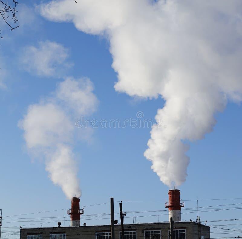 Humo y vapor que vienen de los tubos del sitio de caldera Época en que la calefacción se enciende de invierno Energía termal imagen de archivo libre de regalías