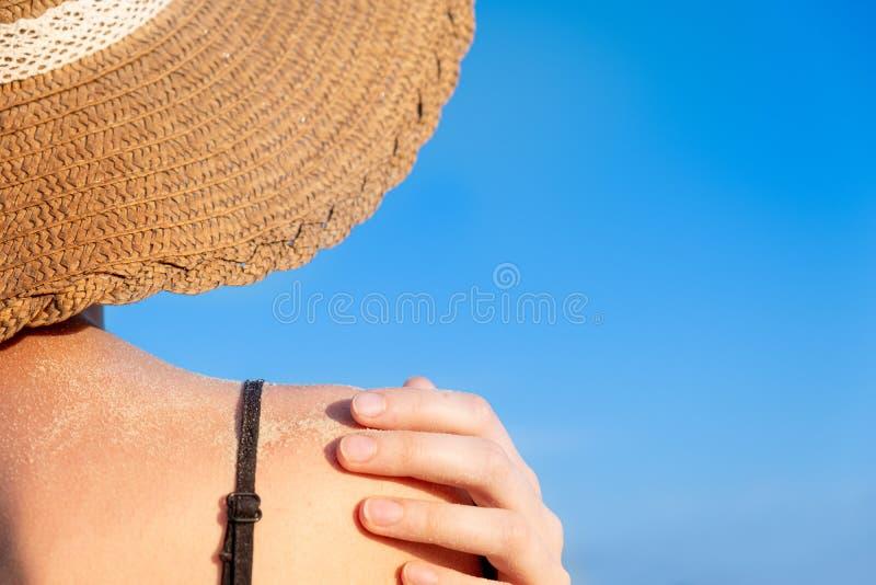 Humor de las vacaciones de verano: hombro femenino cubierto en arena en fondo azul brillante imagen de archivo