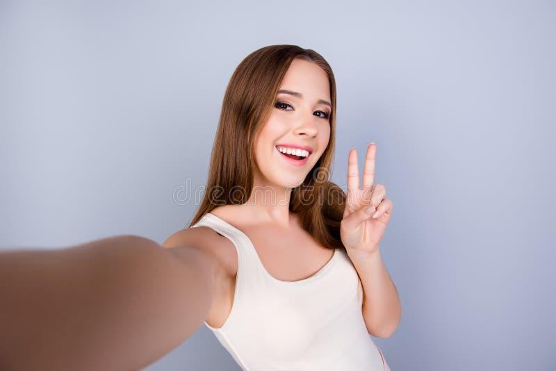 Humor despreocupado y feliz, enrrollado La muchacha sonriente joven linda es makin foto de archivo libre de regalías