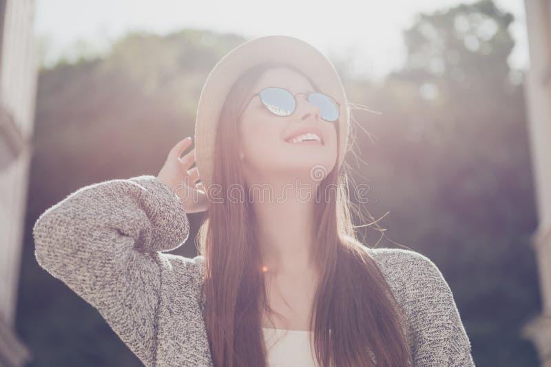 Humor ensolarado do verão Menina de sorriso bonita nova nos óculos de sol e no h fotografia de stock