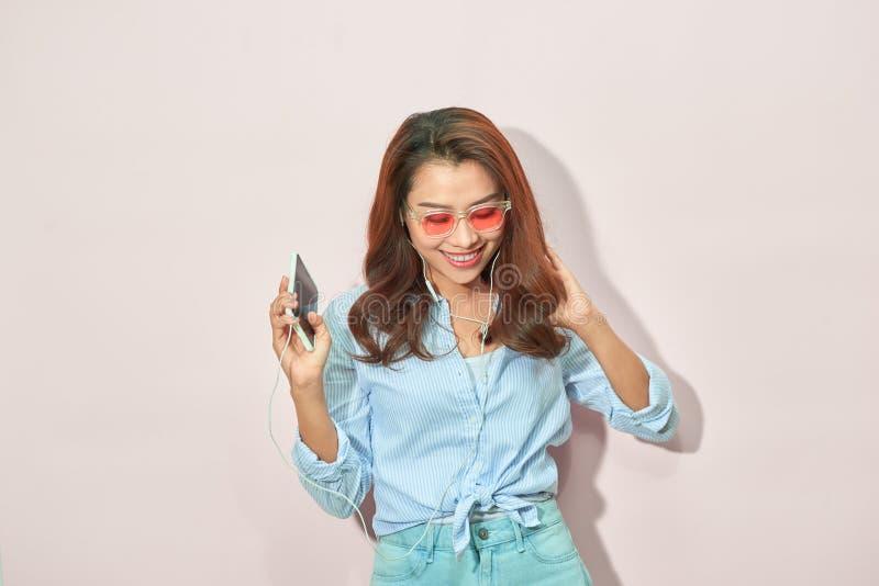 Humor feliz del verano del retrato de la mujer joven alegre con el pelo rizado largo, en gafas de sol en fondo ligero Colores azu imagenes de archivo