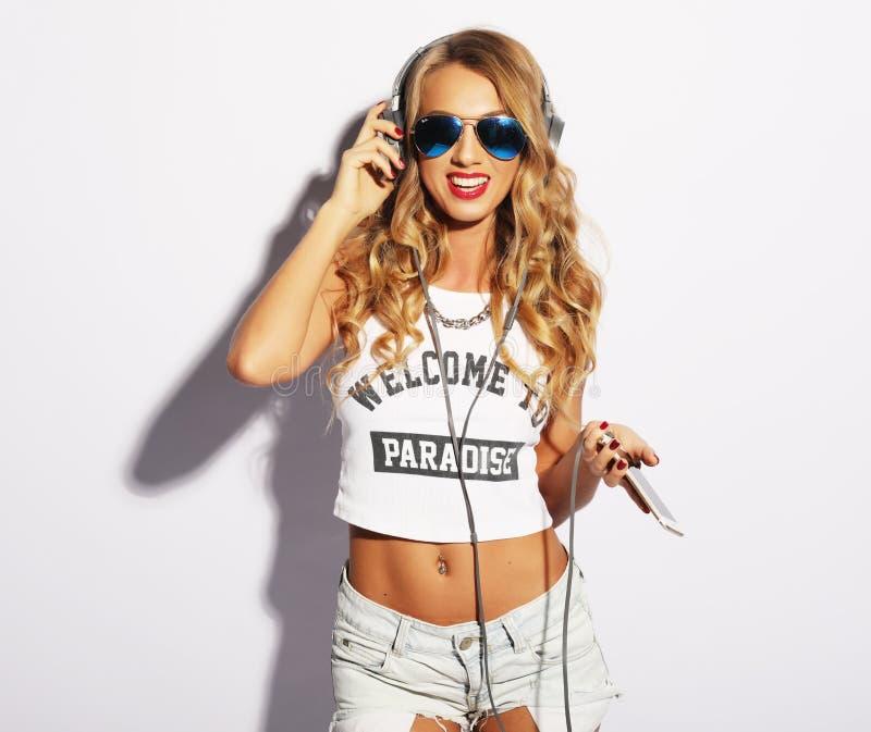 Humor feliz do verão da jovem mulher alegre com cabelo encaracolado longo que escuta a música sobre o fundo branco fotografia de stock