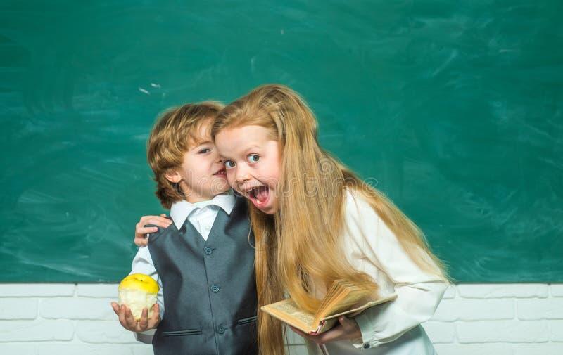 Humor feliz que sorri amplamente na escola Conceito amigável e da amizade Fundo do quadro-negro Rapaz pequeno e bonito engraçados imagem de stock royalty free