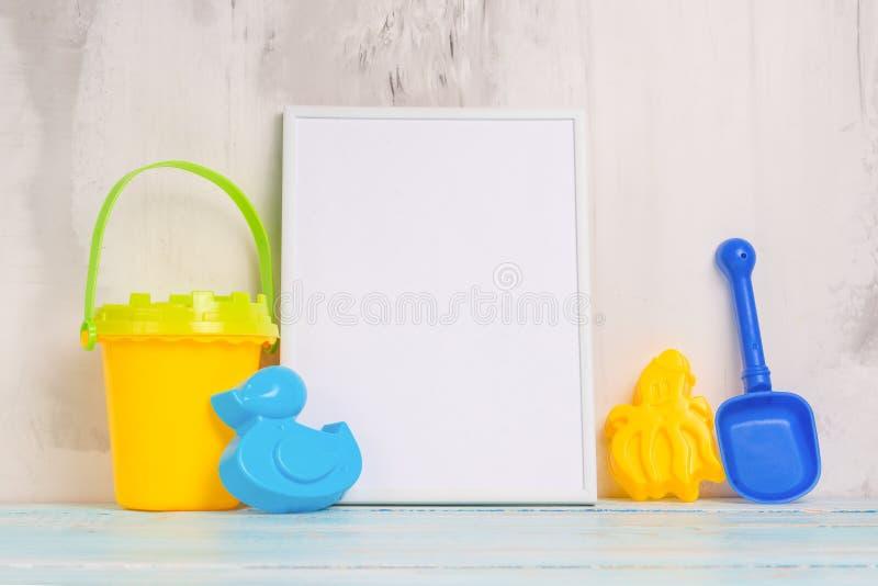 Humor festivo, juguetes del bebé con el marco vacío blanco para el diseño de la disposición Ducha de bebé foto de archivo libre de regalías