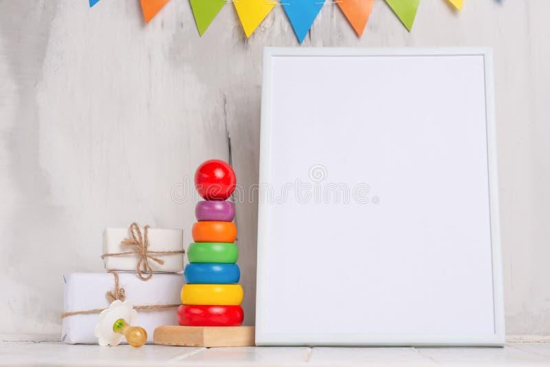 Humor festivo, la guirnalda de los niños con un marco vacío blanco para el diseño, y juguetes con la disposición del regalo Ducha fotos de archivo