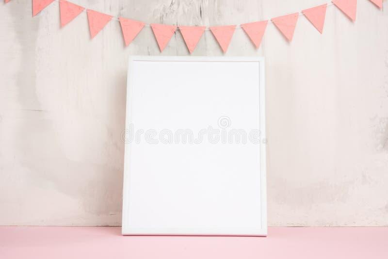 Humor festivo, la guirnalda de los niños en la pared con el marco vacío blanco para el diseño de la disposición Fiesta de bienven foto de archivo