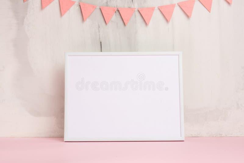 Humor festivo, la guirnalda de los niños en la pared con el marco vacío blanco para el diseño de la disposición Fiesta de bienven fotos de archivo libres de regalías