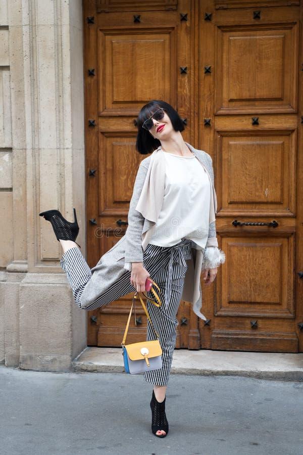 Humor juguetón Señora de moda de la muchacha con el fondo urbano al aire libre de la arquitectura del peinado de la sacudida Mode fotografía de archivo