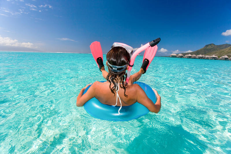 Humor snorkel woman resort. Beautiful turquoise waters and fun woman with snorkel gear near tropical resort stock images
