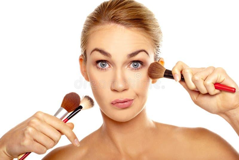 Humoristisch beeld van vrouw met make-upborstels stock fotografie