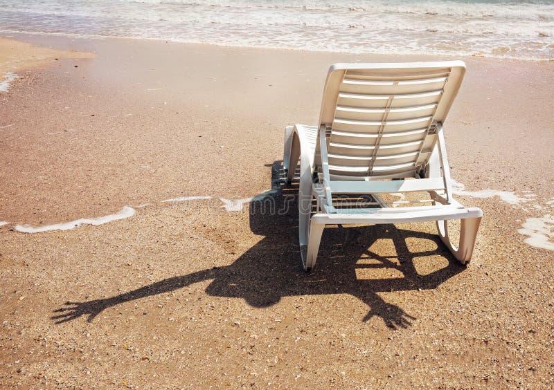 Humoristische scène: vrolijke onzichtbaar somebody met schaduw op het zand royalty-vrije stock afbeeldingen