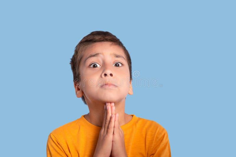 Humoristisk stående av en pojketiggeri för förfrågan på en blå bakgrund i studion arkivfoto