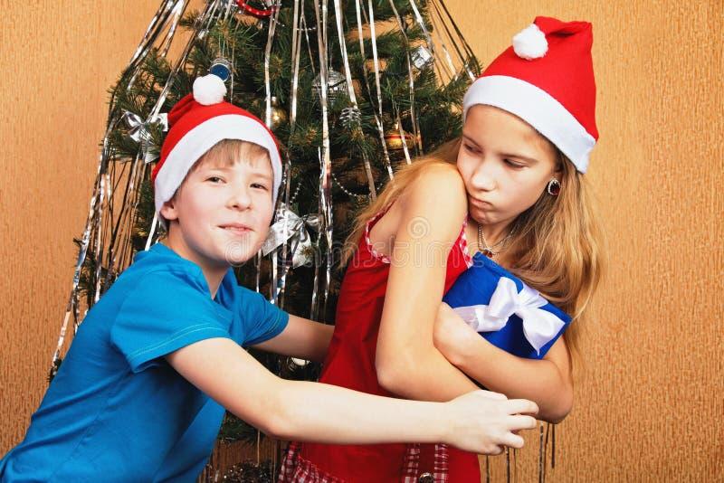 Humoristisk tvist över en gåvaask nära en dekorerad julgran arkivfoto