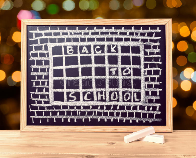 Humorous concept of hate school as prison with text back to school is written in chalkboard, chalks on wooden table over blur. Background, close up stock image