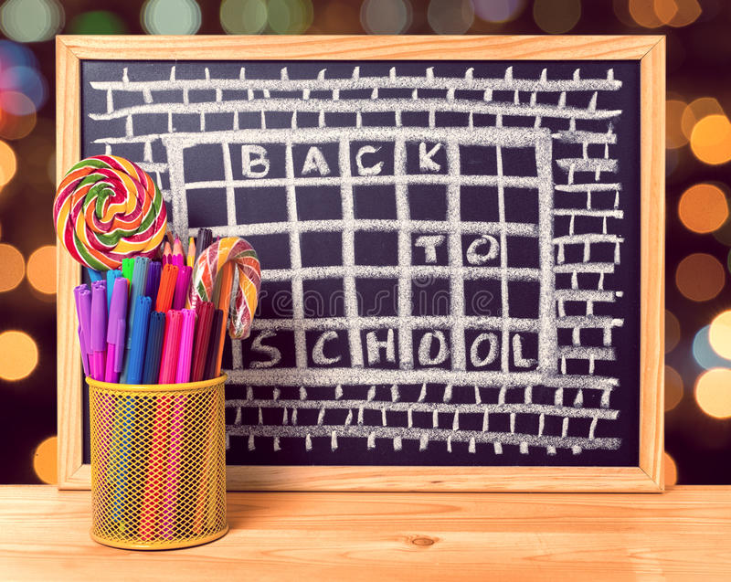 Humorous concept of hate school as prison with text back to school is written in chalkboard, pen holder, peppermint candy on wood. En table over blur background stock images
