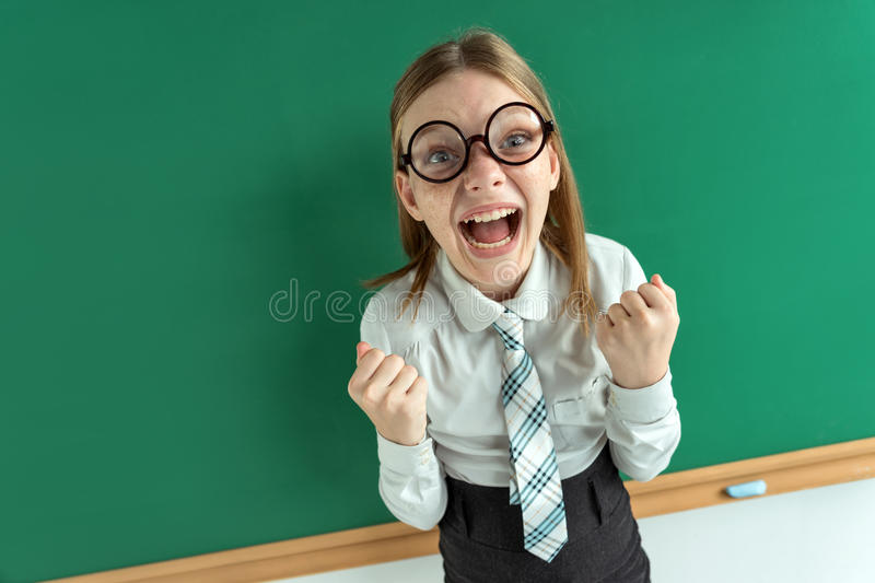 Humorous high angle view of Happy joyful laughing beautiful girl with hands on blackboard in classroom. stock images