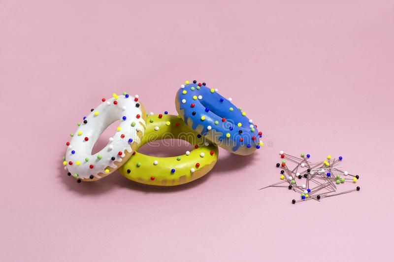 Humorous imitation of donuts from colored bagels with multi-colored pins stock image