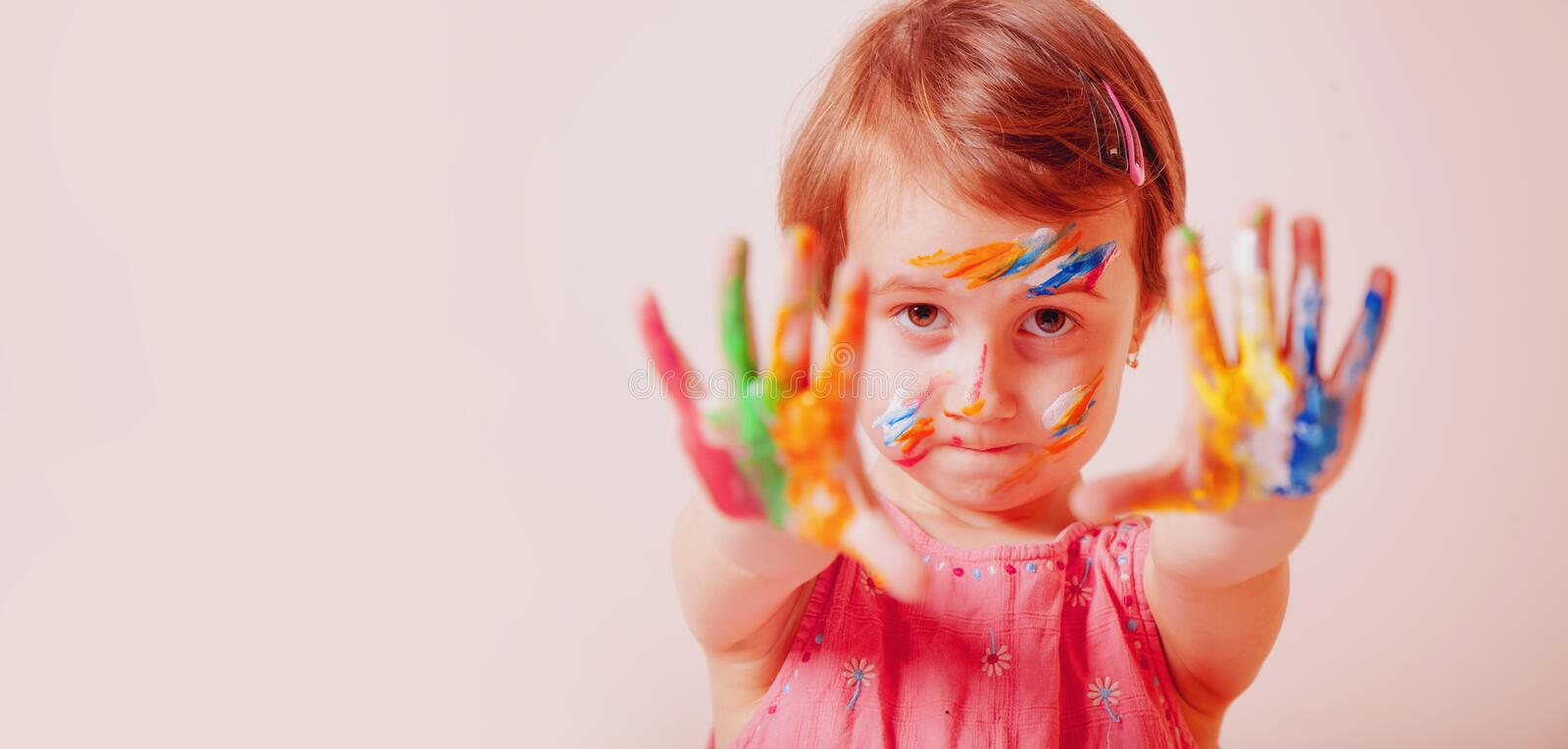 Humorous portrait of cute little child girl with colorful painted faceand hands. Children`s meykap royalty free stock image