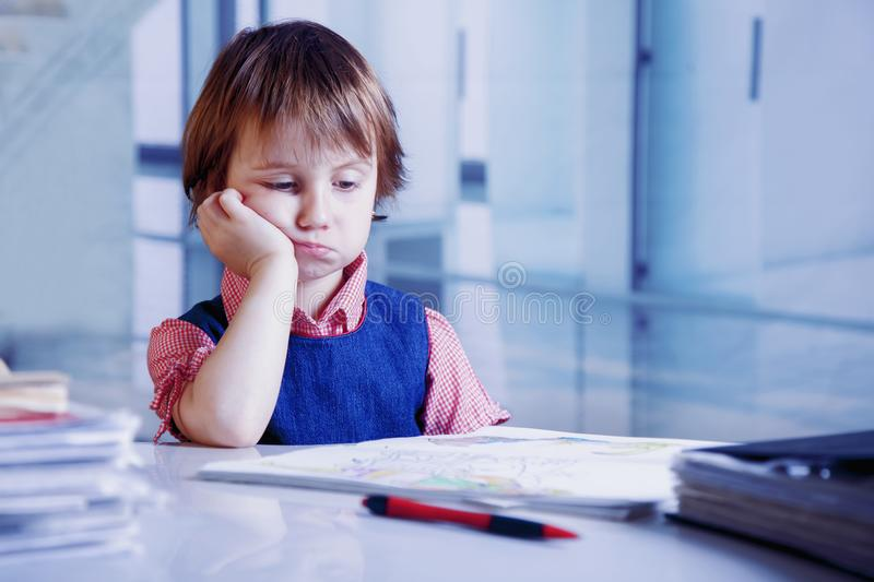 Humorous portrait of tired and exhausted  business child girl working alone in office with a lot of documents. stock image