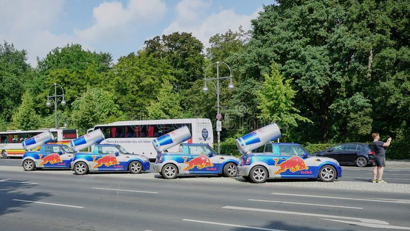 Man takes selfie with four Red Bull Cans on top of BMW Mini Cars stock photography