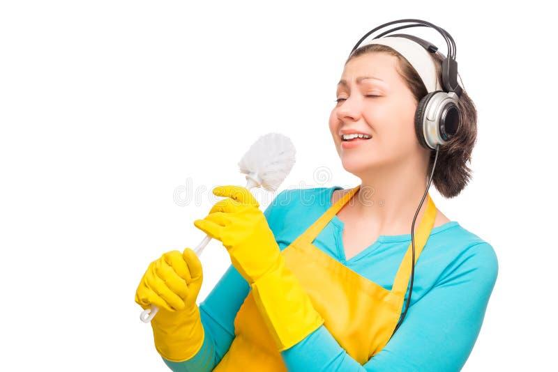 Humorvolle Fotohausfrau mit Kopfhörern und einer Reinigungsbürste lizenzfreie stockfotografie