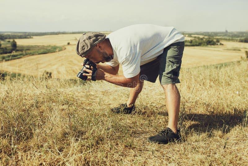 Humorystyczny poj?cie Bardzo emocjonalny fotograf bierze obrazki coś na ziemi Emocja niespodzianka na jego twarzy obrazy stock