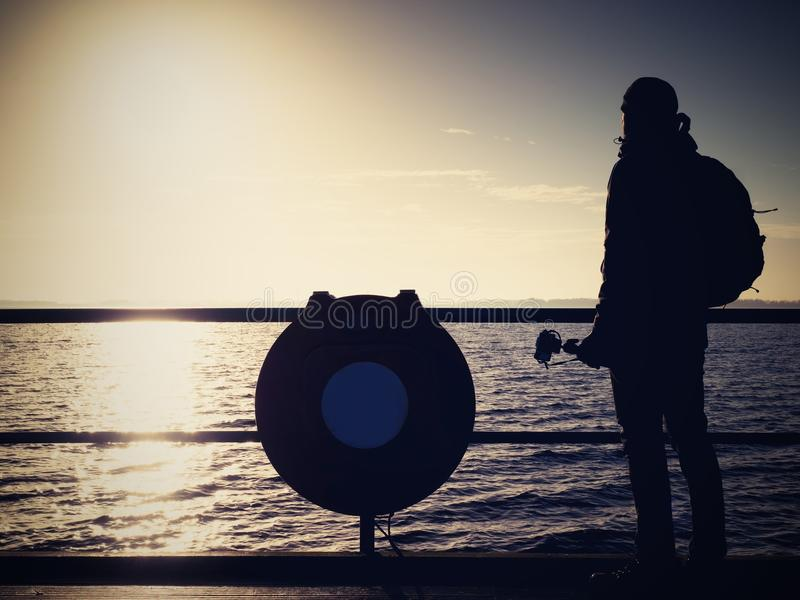 Hunched artist photograph with camera on tripod. Tourist at handrail royalty free stock photo