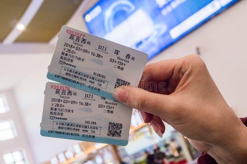 HUNCHUN, JILIN, CHINA - 8 de março de 2018: Dois bilhetes em uma mão do ` s da mulher para o curso pelo trem de alta velocidade C foto de stock