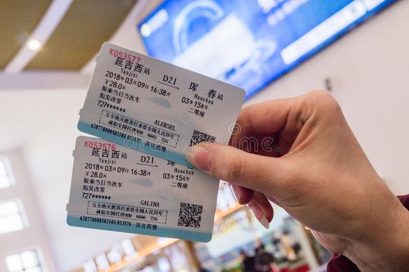 HUNCHUN, JILIN, CHINA - March 8, 2018: Two tickets in a woman`s hand for travel by high-speed train CRH stock photo