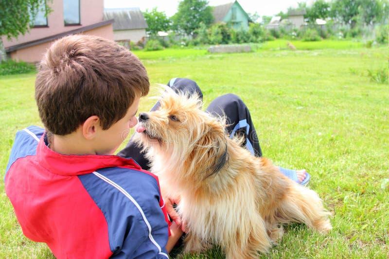 Hund, der das Jungengesicht leckt lizenzfreie stockbilder