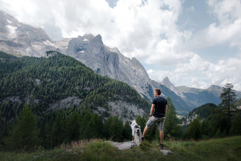 Hund mit einem Mann in den Bergen bei Sonnenaufgang Reise mit einem Haustier lizenzfreie stockfotos