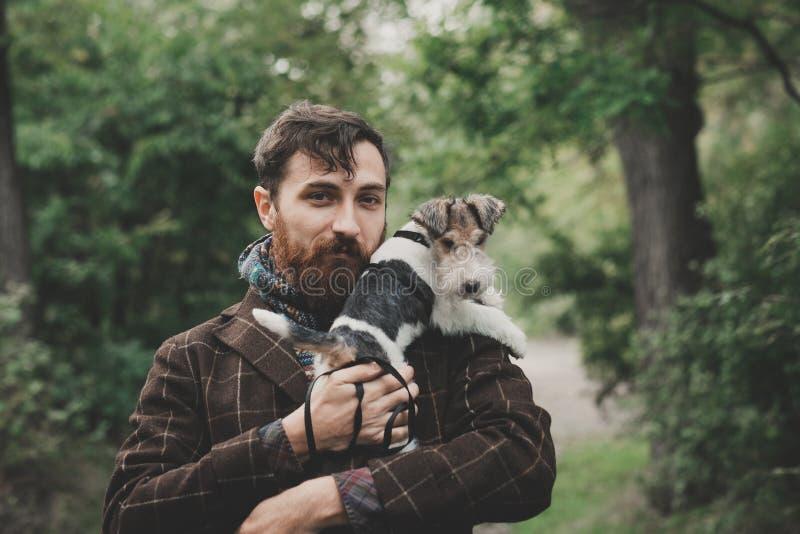 Hund och hans ägare - kall hund och unga mannen som har gyckel i en parkera - begrepp av kamratskap, husdjur, samhörighetskänsla royaltyfria foton