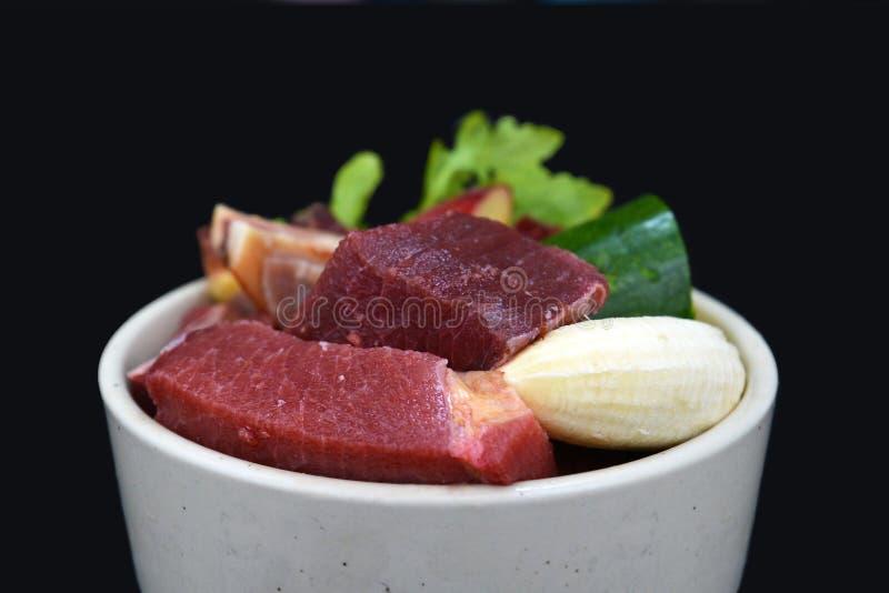 Hunde- oder Katzenschüssel gefüllt mit einer Mischung aus biologisch geeigneten Rohkost, die Fleischstücke, Obst und Gemüse enthä stockfotos