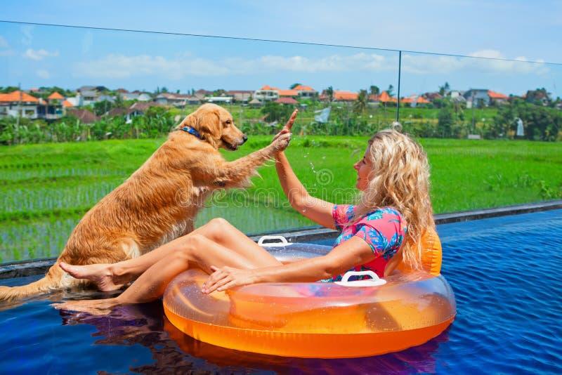 Hunden ger höjdpunkt fem till lycklig flickasimning i pöl royaltyfri foto