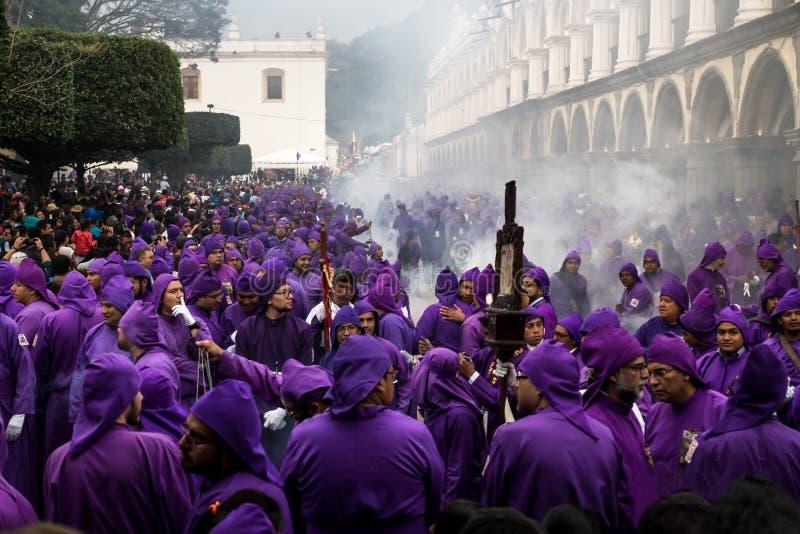Hunderds de homens vestidos com robe roxos na procissão San Bartolome de Becerra no prefeito da plaza, Antígua, Guatemala imagem de stock