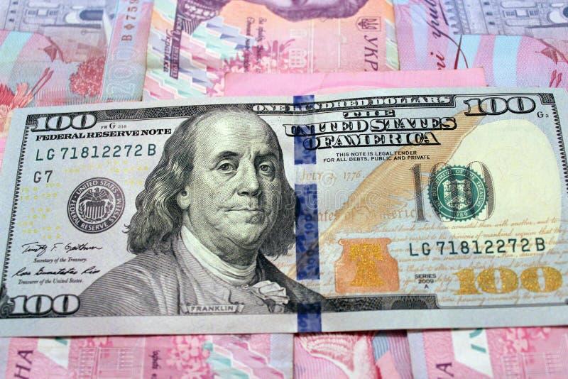 Hundert Dollar auf den ukrainischen grivnas Banknoten stockfotografie