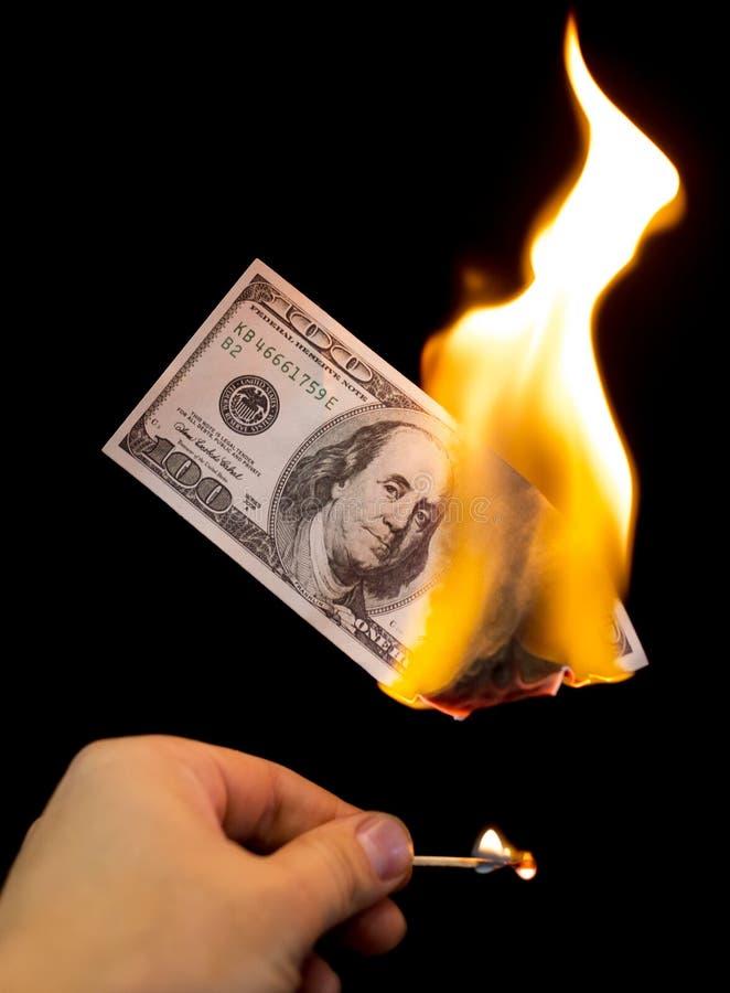 Hundert Dollar brennen in einem Feuer auf einem schwarzen Hintergrund stockfoto